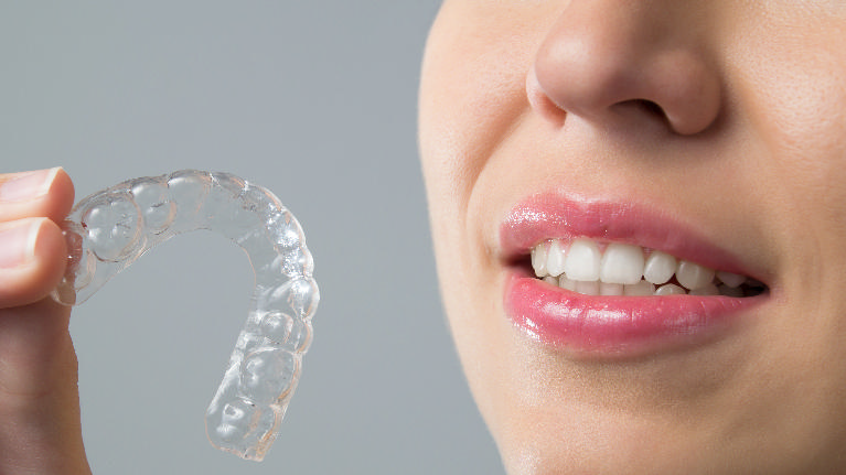 Woman posing with ClearCorrect Tray | Clear Orthodontics in Cumberland IN